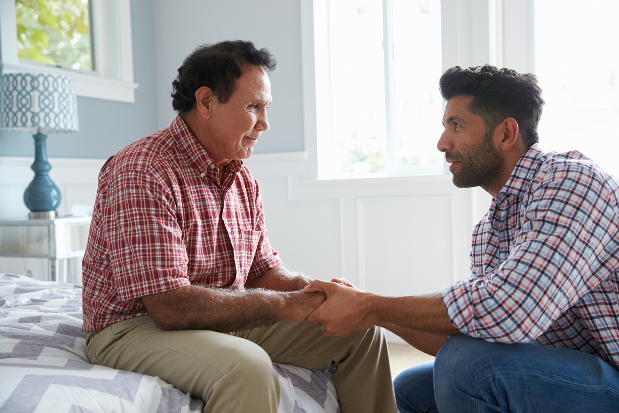 Adult Son Comforting Father Suffering With Dementia